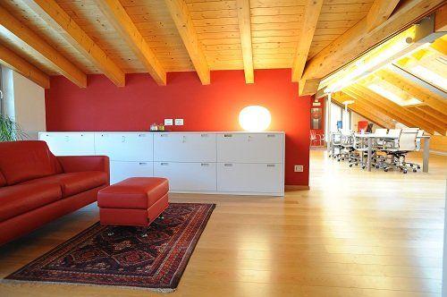 Studio con tetto di legno, parete rossa, mobili bianchi, sofà rosso