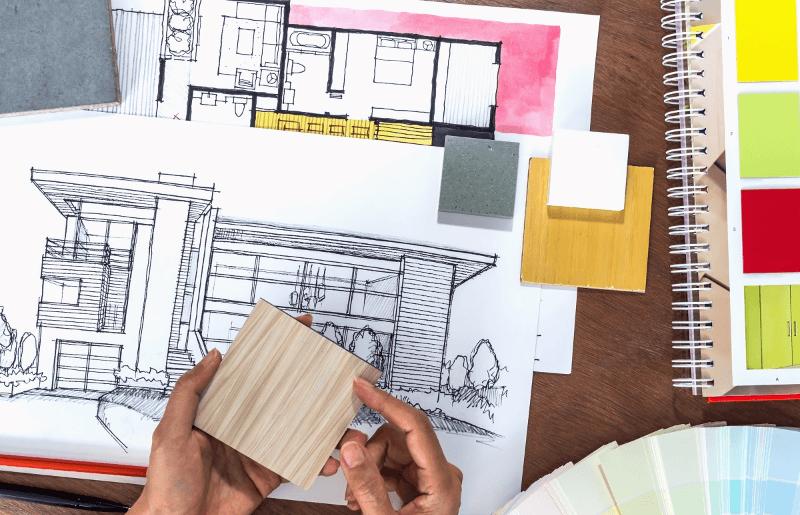 una mano tiene del legno e sullo sfondo uno schizzo di una casa
