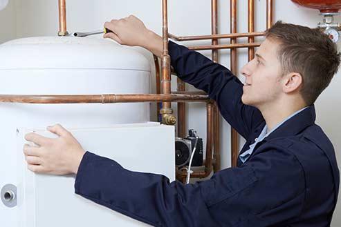 addetto mentre installa una caldaia