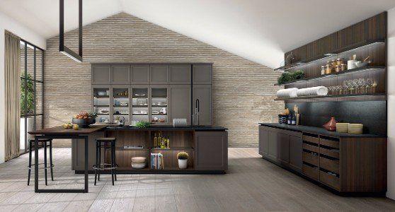 Cucina sala da pranzo spaziosa con mobili grigie e bruni e tavola centrale di lavoro