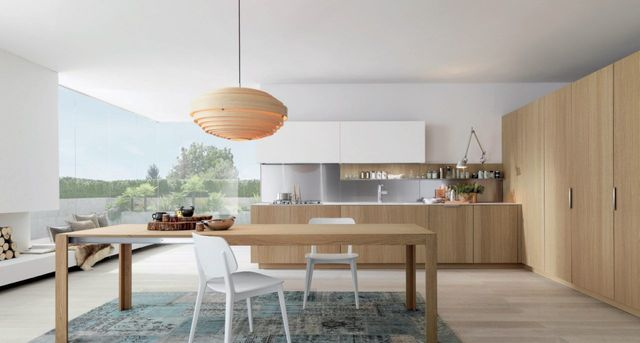 Cucina bianca completamente accessoriata, tavola nella zona adiacente, grandi finestre sul giardino
