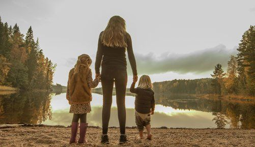 A mother holding hands with 2 children by a lake