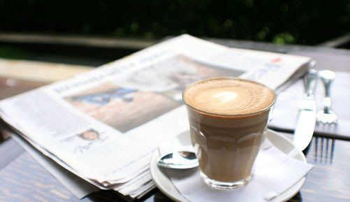 Cup of coffee next to a newspaper