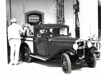 foto d'epoca con un'auto e un tecnico di spalle