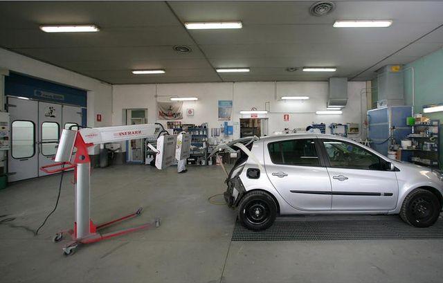 Interno dell'officina con auto in fase di riparazione