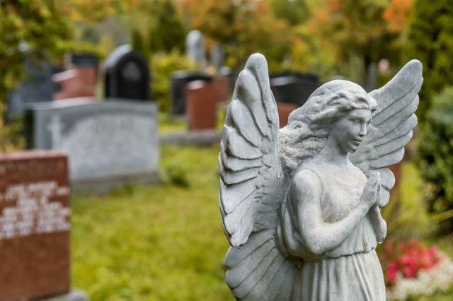 uno statua di una donna angelo in un cimitero
