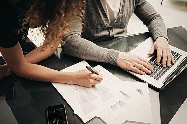 una donna e un uomo stanno scrivendo, la prima sul foglio e, il secondo al computer