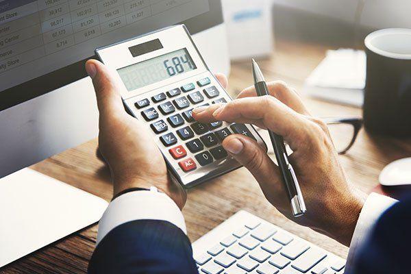 un commercialista con penna e calcolatrice in mano mentre sta facendo dei calcoli