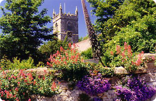 Old stone clock tower in lovely gardens
