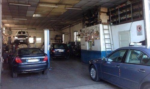 Campo lungo dell'interno dell'officina con tre auto parcheggiate