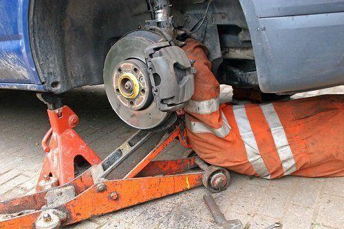 un meccanico sotto una macchina mentre cambia una gomma