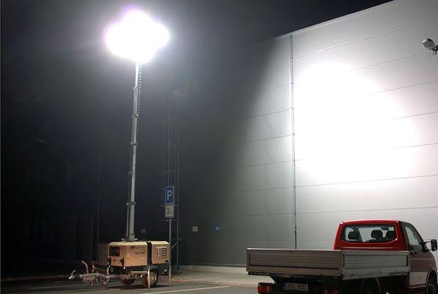un gruppo elettrogeno che alimenta un lampione acceso e di fianco un camioncino da lavoro di color rosso