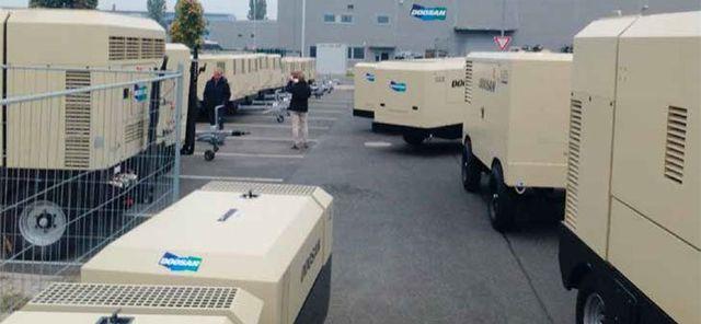 serie di gruppi elettrogeni nel parcheggio dell'azienda e in lontananza si vedono due uominii