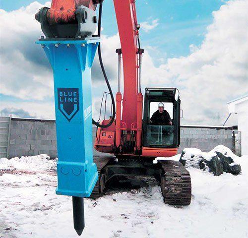 una demolitrice di color rosso con percussore di color blu in una strada innevata