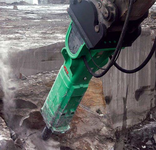 un demolitore verde di una scavatrice che sta perforando la roccia