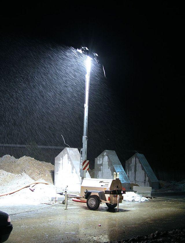 un gruppo elettrogeno e un lampione acceso in un cantiere visto da lontano
