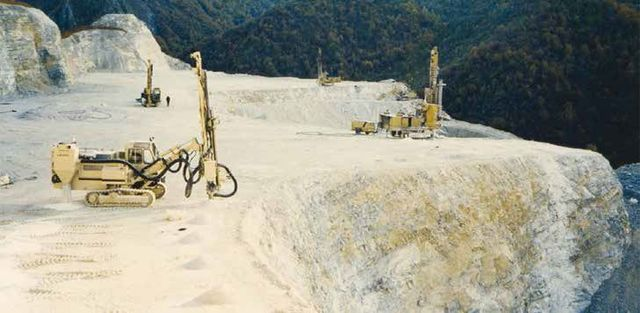 delle scavatrici gialle con percussore su un rilievo montuoso e dietro vista di una pineta
