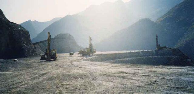scavatrici viste in lontananza su una strada di  montagna