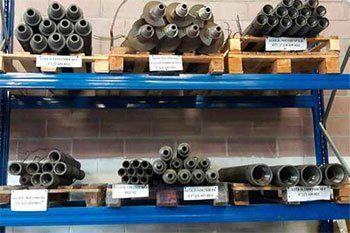 esposizione su scaffali blu con sopra dei bancali di strutture in ferro per perforatrici