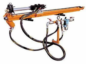 una perforatrice di color arancione e dei tubi in gomma a lei collegati