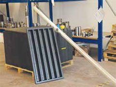 un asse di metallo quadrata e una trave di legno obliqua vicino a degli scaffali blu