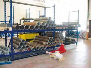 serie di grossi tubi in ferro su uno scaffale blu