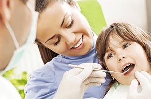 Una donna analizza i denti di un bambino a bocca aperta