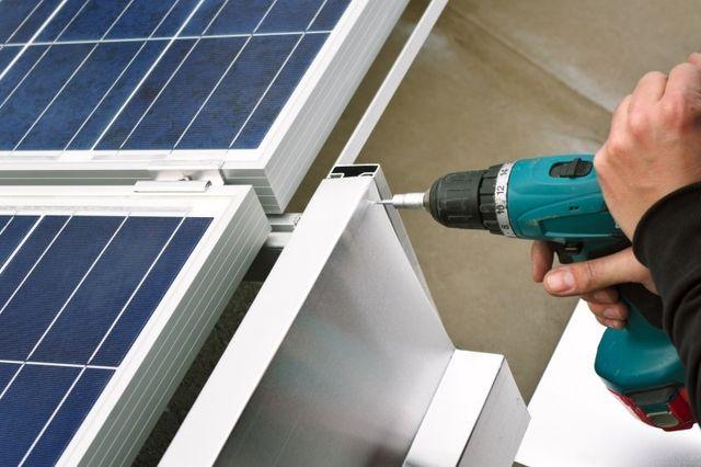 un trapano che avvita un supporto per dei pannelli solari