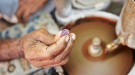 anziana donna che crea gioielli con pietra viola in mano
