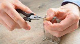 mani che riparano una collana con pinza e gioiello