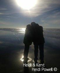Heidi & Kent Powell kissing on the beach