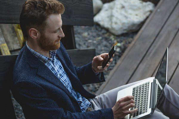 Man mutli-tasking with smartphone and laptop