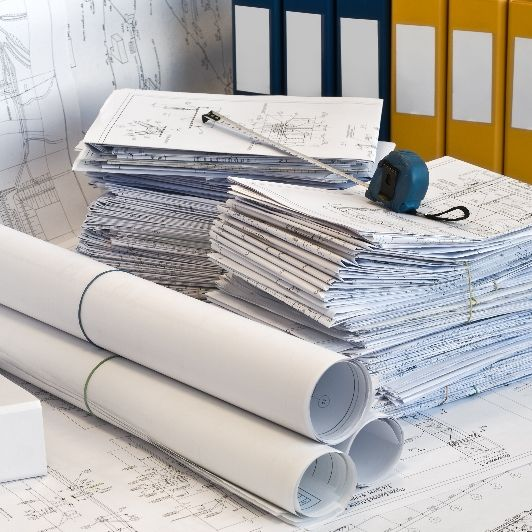 stack of blueprints and other drafting paperwork