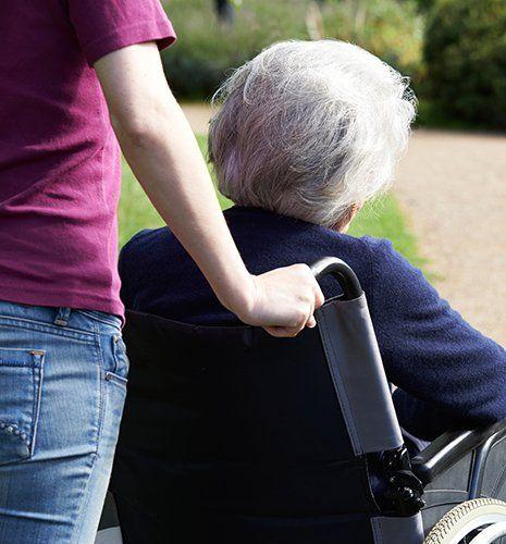 una donna che spinge una signora anziana con i capelli grigi su una sedia a rotelle