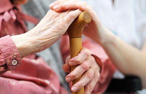 una signora anziana con la mano sopra un bastone e sopra la mano di un'altra donna