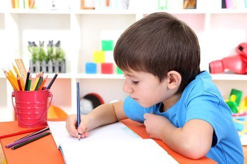 Young boy writing on notebook
