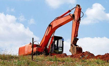 large digger at work in field