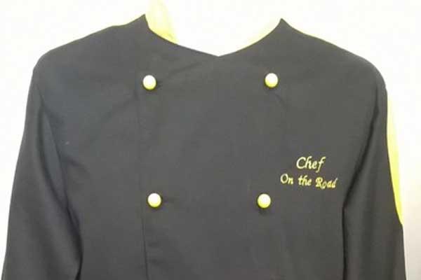 Uniforme da chef nera con rifiniture e bottoni gialli, posta su un manichino