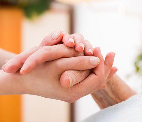 una mano di una donna giovane che tiene quella di un' anziana