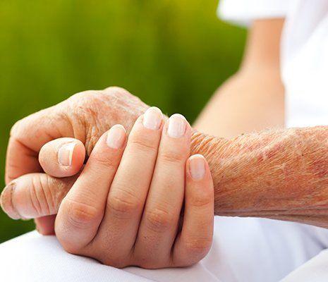 una mano di una donna che tiene calorosamente quella di una donna anziana e dietro uno sfondo verde