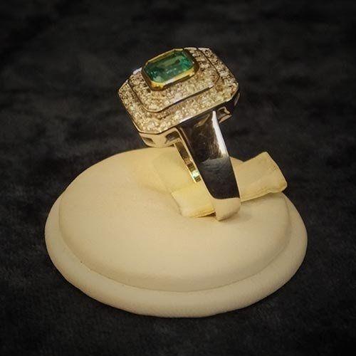 un anello di diamanti con una pietra verde