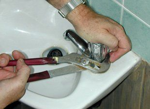 Plumber using wrench to tighten tap on bathroom sink