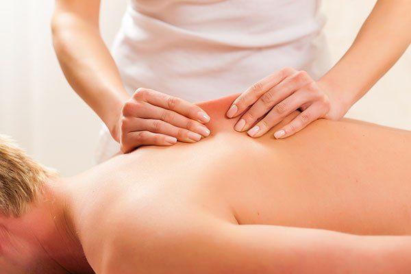 persona che massaggia un paziente su un lettino
