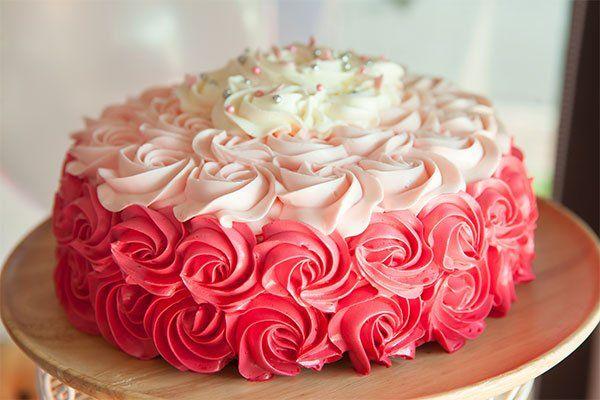 Torta fatto di rose di crema di tre colori del rosa al bianco
