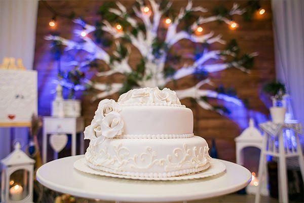 Torta di nozze di due piani,abbellita con due rose bianche di