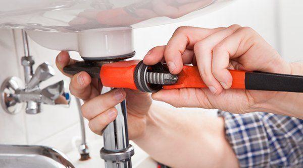 due mani di un idraulico che stanno riparando con un pappagallo arancione un tubo in acciaio del lavandino di un bagno