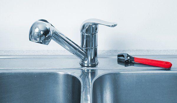 un rubinetto d' acciaio e accanto una pinza rossa