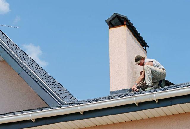 un uomo chinato su un tetto al lavoro su un camino