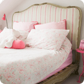 A wooden bed frame and padded headboard