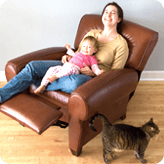 A parent and child relaxing at home, laminate flooring beneath their reclining chair